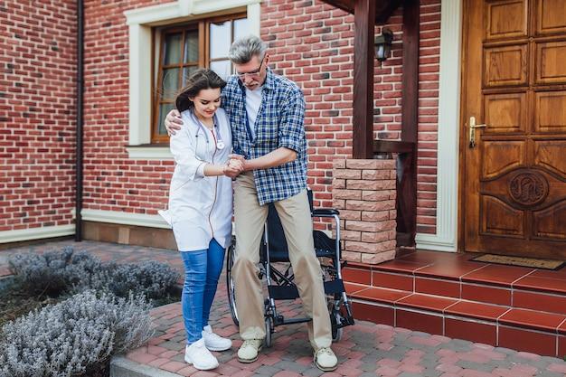 Senior hombre llegó a su casa en silla de ruedas con enfermera