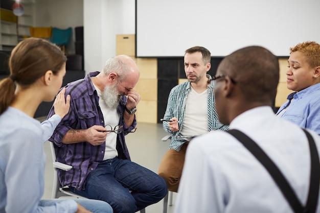 Senior hombre llorando en grupo de apoyo