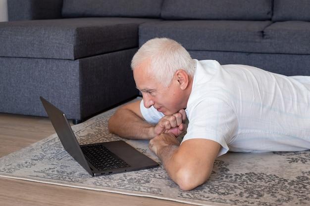 Senior hombre maduro con computadora trabajando en línea o viendo seminarios web en casa