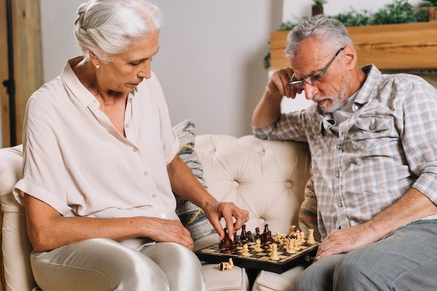 Senior hombre mirando a su esposa jugando al ajedrez