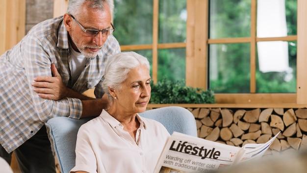 Senior hombre mirando a su esposa leyendo el periódico cerca de la ventana