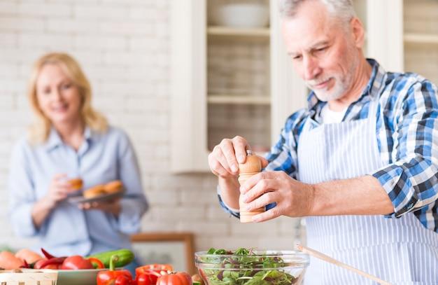 Senior hombre moliendo pimienta para ensalada y su esposa disfrutando de los muffins en el fondo en la cocina