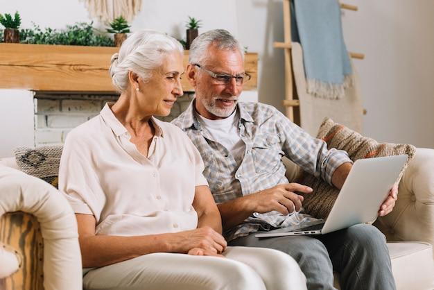 Senior hombre mostrando algo en la computadora portátil a su esposa