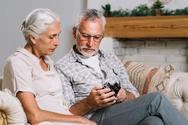 Senior hombre mostrando la cámara a su esposa sentada en el sofá