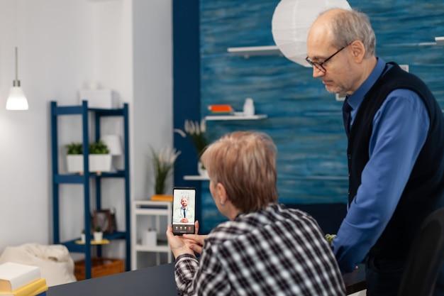 Senior hombre y mujer enfermos hablando con el médico durante la videollamada
