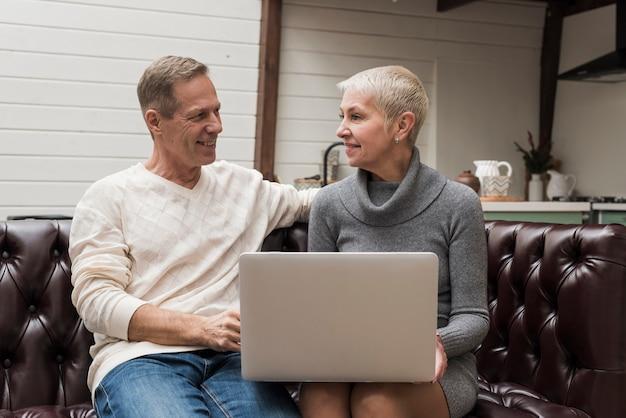 Senior hombre y mujer mirando a través de su computadora portátil