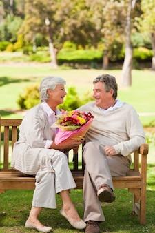 Senior hombre ofreciendo flores a su esposa