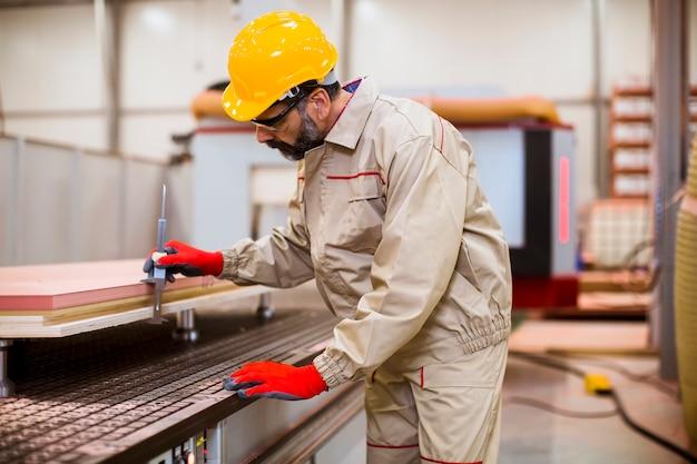 Senior hombre operando unidades de máquina en fábrica moderna de pie junto al panel de control