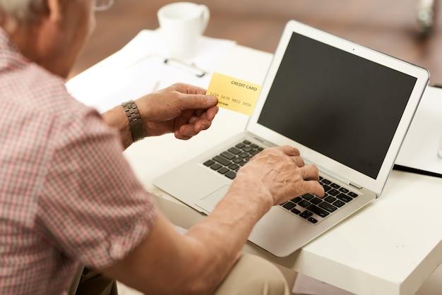 Senior hombre pagando con tarjeta de crédito