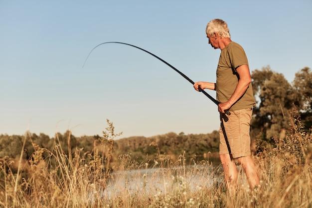 Senior hombre pesca, sosteniendo la caña de pescar en las manos, vistiendo camiseta verde y corta, mirando bobber y sacando peces, de pie en la orilla del lago.