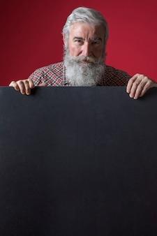 Senior hombre de pie detrás del cartel negro sobre fondo rojo