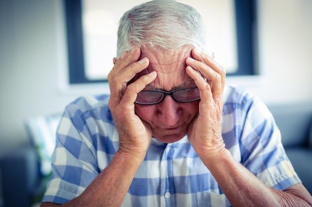 Senior hombre que sufre de dolor de cabeza
