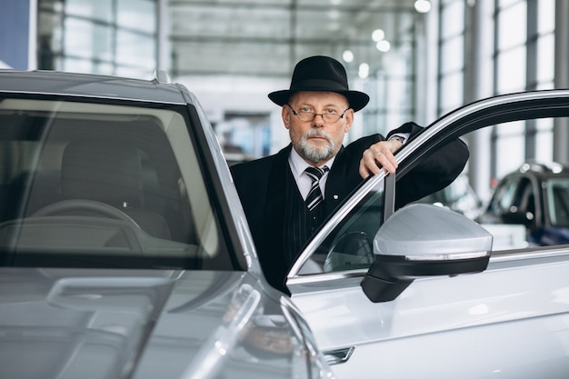 Senior hombre en una sala de exposición de automóviles elegir un automóvil