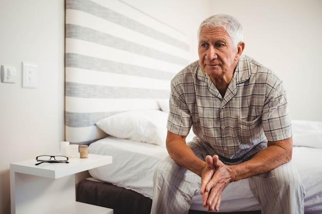 Senior hombre sentado en la cama en el dormitorio