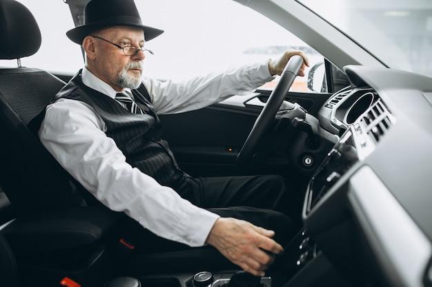 Senior hombre sentado dentro de un auto