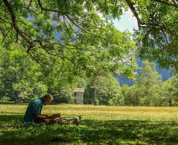Senior hombre sentado en la hierba leyendo un libro relajado