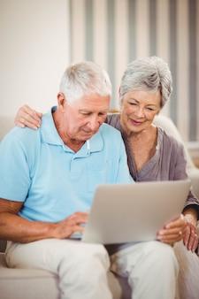 Senior hombre sentado con una mujer en el sofá y usando la computadora portátil en la sala de estar