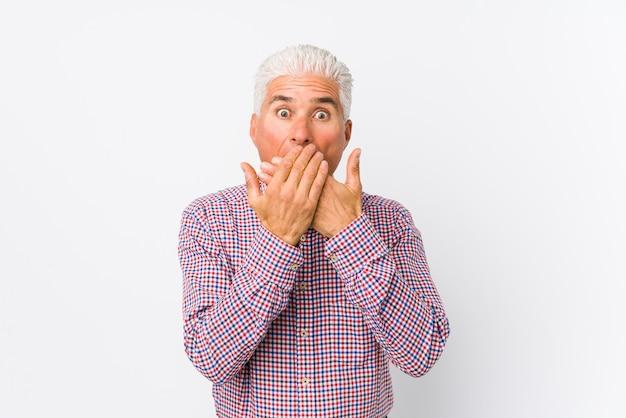 Senior hombre sorprendido cubriendo la boca con las manos