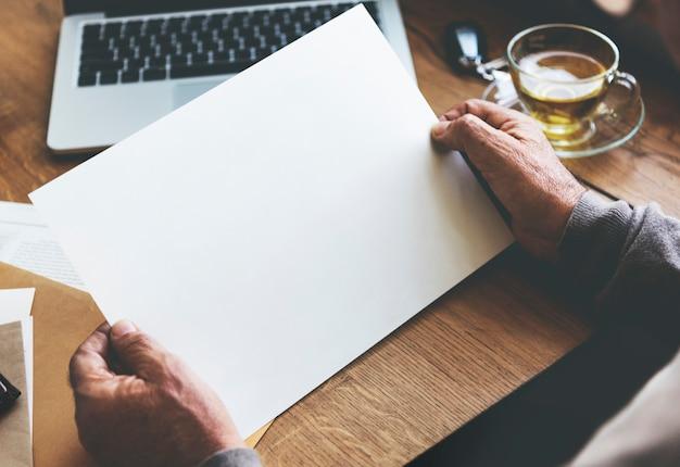 Senior hombre sosteniendo un papel en blanco