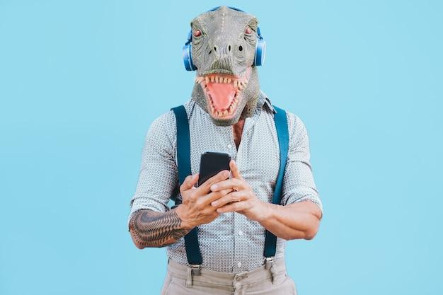 Senior hombre tatuado con máscara t-rex usando teléfono inteligente mientras escucha música