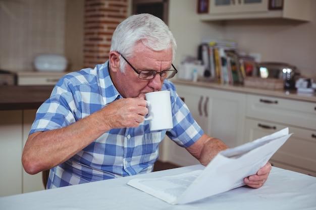 Senior hombre tomando café mientras leía el periódico