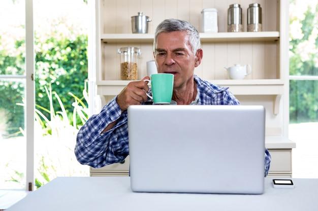 Senior hombre tomando café mientras usa la computadora portátil