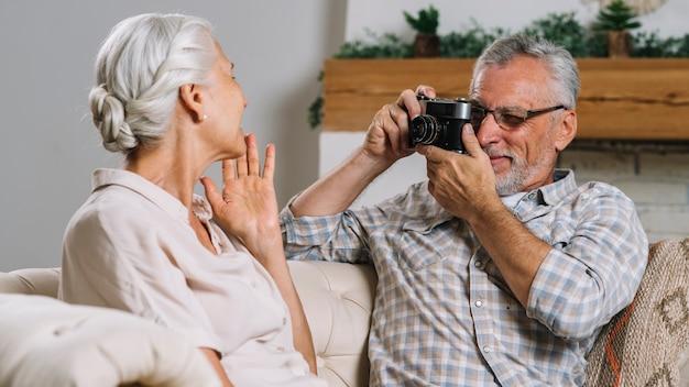 Senior hombre tomando foto de su esposa de cámara