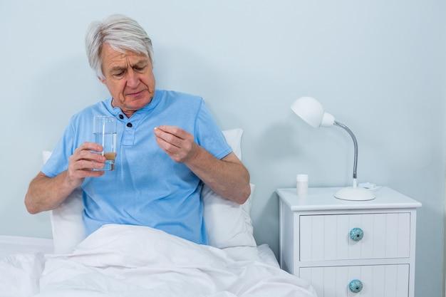 Senior hombre tomando pastillas en casa