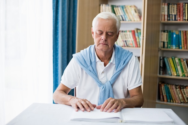 Senior hombre usando braille para leer