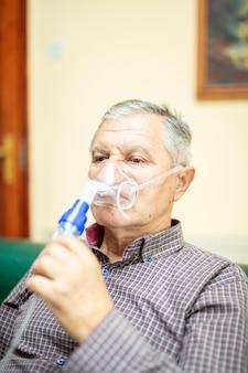 Senior hombre usando equipo médico para inhalación con máscara respiratoria, nebulizador