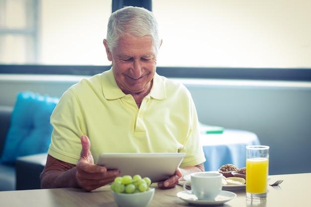 Senior hombre usando tableta digital mientras desayunando