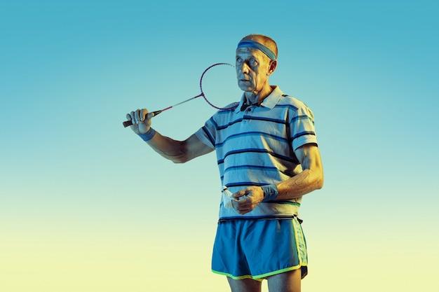 Senior hombre vestido con ropa deportiva jugando bádminton sobre fondo degradado, luz de neón.