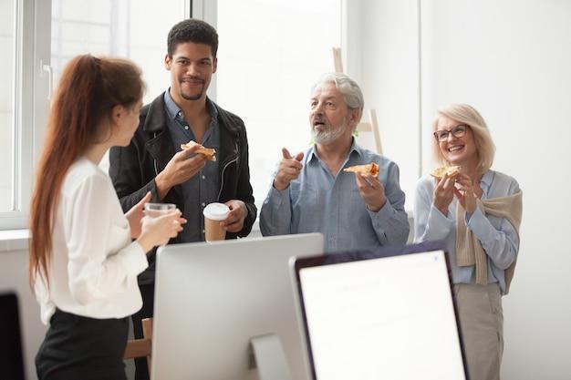 Senior y jóvenes colegas hablando mientras comen pizza en la oficina