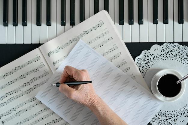 Senior mano sostiene un bolígrafo y escribe notas en el pentagrama junto a las teclas del piano y una taza de café
