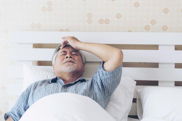 Senior masculino asiático sufriendo de mal dolor en su pecho ataque al corazón en casa