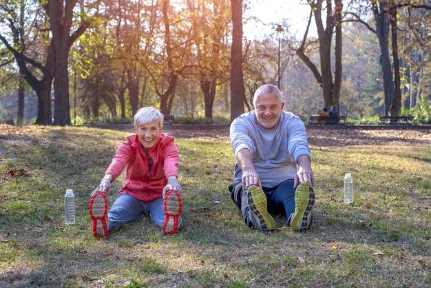 Senior masculino y femenino haciendo ejercicio en el parque en otoño