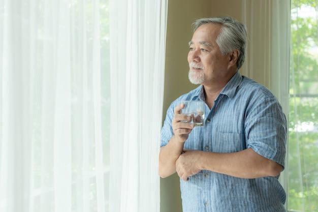 Senior masculino se siente feliz bebiendo agua fresca en la mañana, disfrutando el tiempo en su casa
