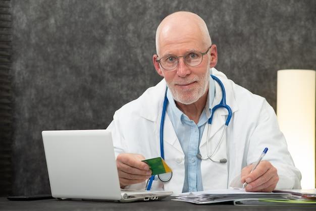 Senior médico barbudo con tarjeta de seguro de salud