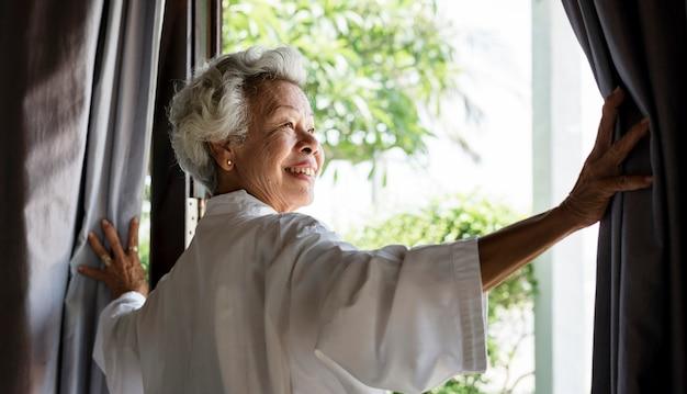 Senior mujer abriendo las cortinas