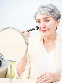 Senior mujer asiática aplicando base en la mejilla con un pincel de maquillaje mientras está sentada sola frente a un espejo.