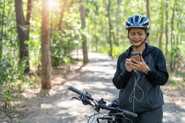 Senior mujer asiática en bicicleta en el parque