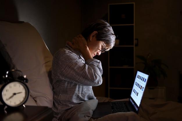 Senior mujer asiática con dolor muscular y doloridos por el uso del portátil en la cama