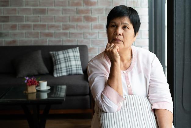 Senior mujer asiática pensando y mirando hacia los lados, pensando y preguntándose