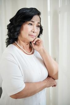 Senior mujer asiática de pie junto a la ventana en casa y mirando a otro lado