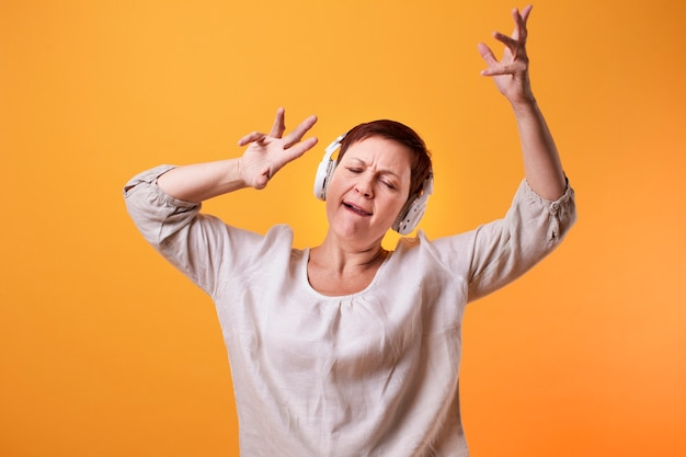 Senior mujer bailando y escuchando música en auriculares