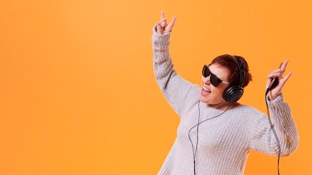 Senior mujer bailando y escuchando música con espacio de copia