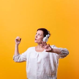 Senior mujer bailando y escuchando música
