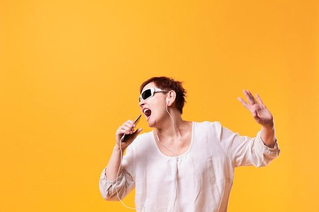 Senior mujer cantando y escuchando música