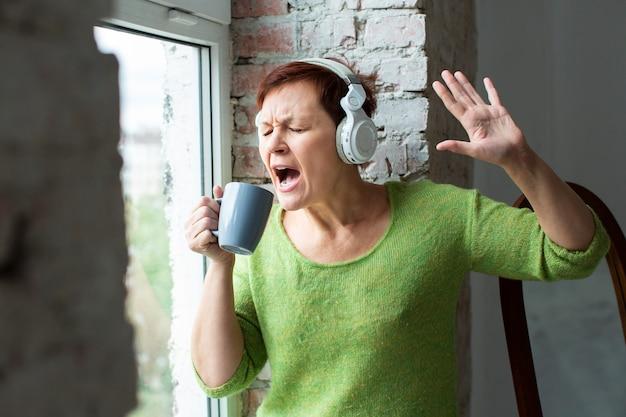 Senior mujer cantando en la taza de café