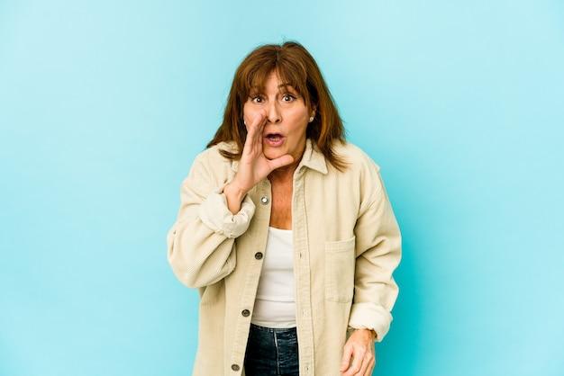 Senior mujer caucásica aislada está diciendo una noticia secreta de frenado en caliente y mirando a un lado